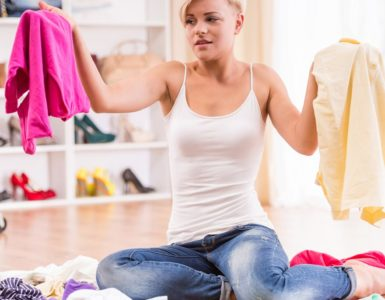 woman decluttering closet and deciding which clothes to get rid of