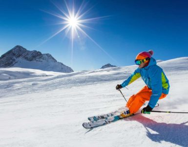 person in a blue coat and orange pants skiing down the mountain under a bright sun