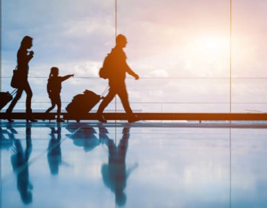 silhouettes of family with child pulling luggage in an airport, traveling