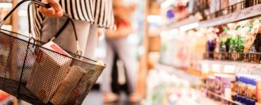 woman shopping in a grocery store aisle, closeup of basket