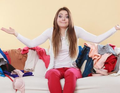 woman sitting on a couch shrugging while surrounded by extra clothes